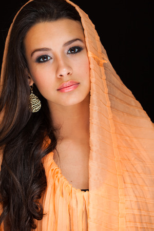 mixed race girl: Beautiful young woman wearing a shawl on a black background.