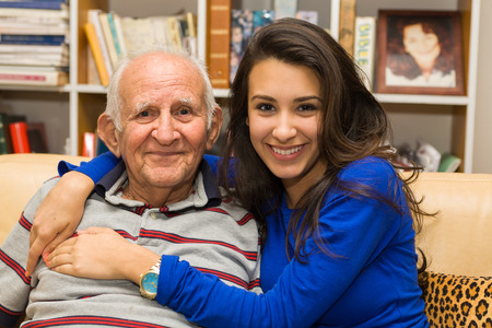 Elderly eighty plus year old man with granddaughter in a home setting. photo
