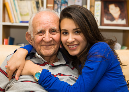 granddaughter: Elderly eighty plus year old man with granddaughter in a home setting.