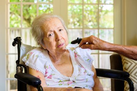 Ältere und achtzig Jahre alte Frau in einem Rollstuhl in einer Umgebung zu Hause zugeführt.