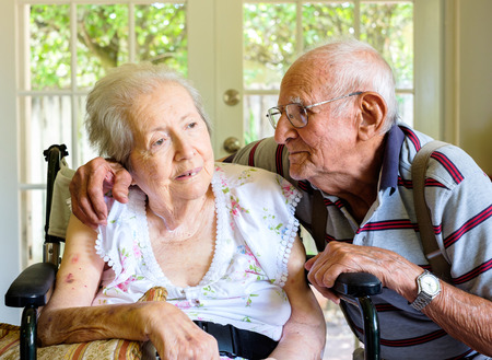 Elderly eighty plus year old woman in a wheel chair in a home setting with her husband. photo