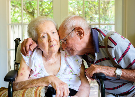Ältere und achtzig Jahre alte Frau in einem Rollstuhl in einer Umgebung zu Hause mit ihrem Ehemann.