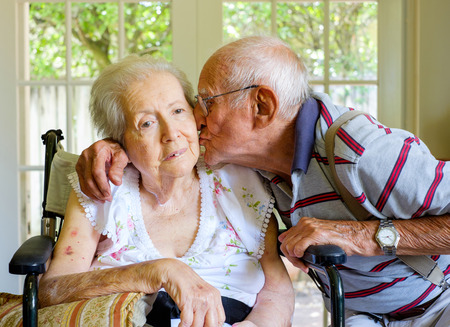 achtzig: �ltere und achtzig Jahre alte Frau in einem Rollstuhl in einer Umgebung zu Hause mit ihrem Ehemann.