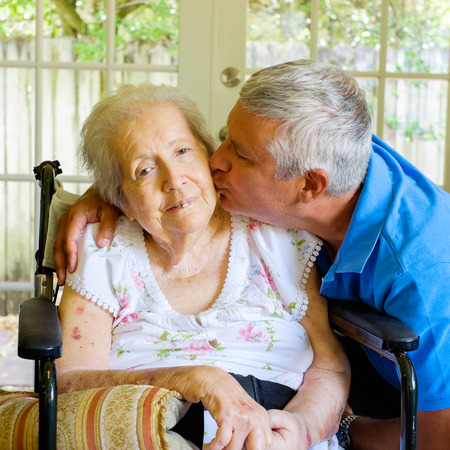 the elderly residence: Elderly eighty plus year old woman in a wheel chair in a home setting with her son.