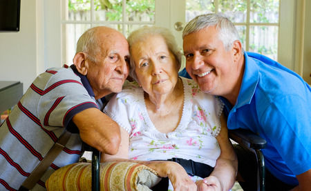 the elderly residence: Elderly eighty plus year old woman in a wheel chair in a home setting with her husband and son.