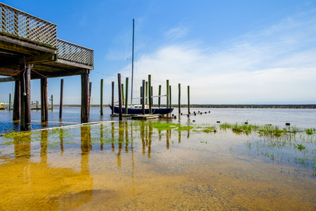 mississippi: Gulf coast shoreline with sailboat in Mississippi. Stock Photo