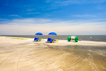 recliner: Gulf coast beach in Gulfport, Mississippi with lounge chairs along the shoreline. Stock Photo