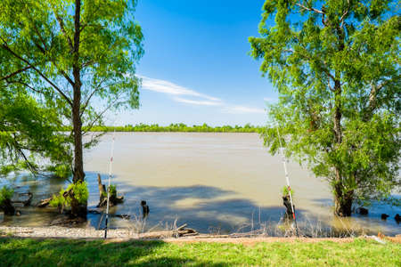 mississippi river: Fishing rods on the Mississippi River in a popular park in New Orleans, Louisiana. Stock Photo