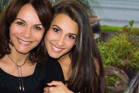 Mutter und Tochter in einer liebevollen Pose im Freien.