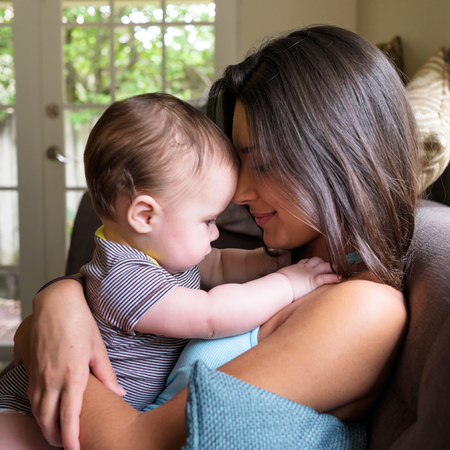 Cute baby boy with pretty young woman in a home setting  photo