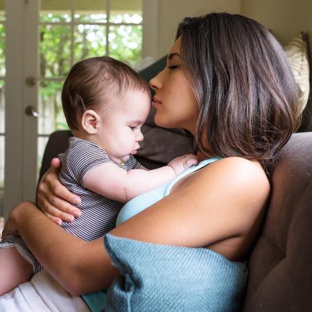 niños latinos: Bebé lindo con la mujer joven y bonita en un ambiente de hogar