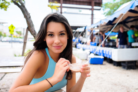Beautiful young woman enjoying a snack in a outdoor farmers market  photo