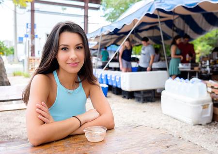Mooie jonge vrouw genieten van een hapje in een outdoor boerenmarkt Stockfoto