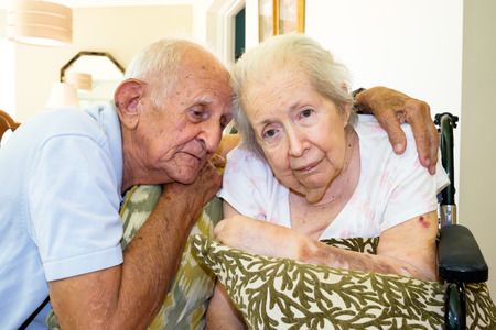 aging: Elderly eighty plus year old woman in a wheel chair in a home setting with her husband  Stock Photo
