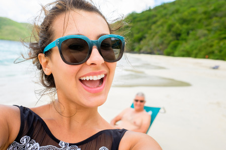 indian ethnicity: Beautiful young multicultural woman taking a selfie on a Caribbean beach.