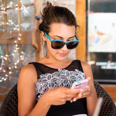 latin american ethnicity: Beautiful girl texting on a cell phone outdoors.