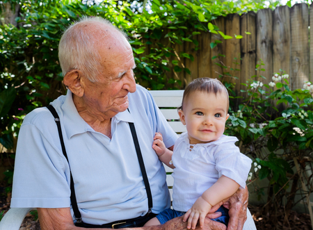 senior citizen: Cute baby boy with great grandfather outdoors.
