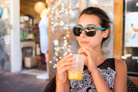 sipping: Beautiful girl sipping a smoothie outdoors in a restaurant setting.