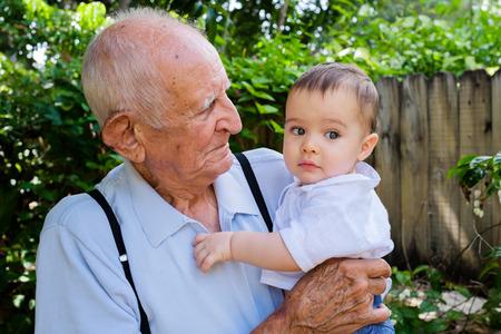 niños latinos: Bebé lindo con gran abuelo al aire libre.