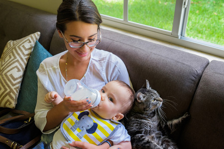 Cute baby boy being fed milk by a pretty young woman in a home setting. photo