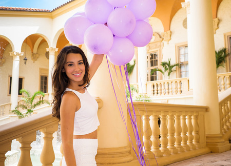indian summer: Beautiful young woman in a outdoor courtyard setting holding balloons.