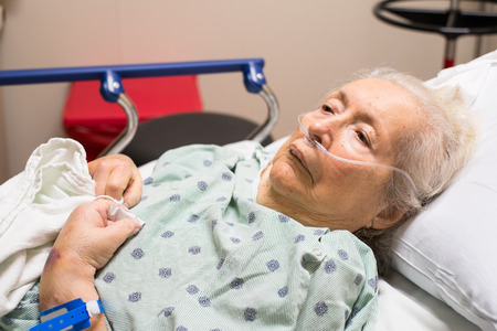 hospitalized: Elderly eighty plus year old woman in a hospital bed.