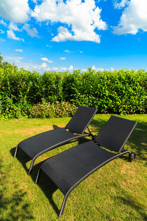 back yard: Wicker lawn chairs in a back yard residence. Stock Photo