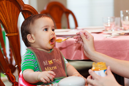 Hungry baby boy being fed a meal in a home setting. photo