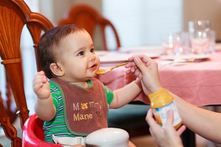 Hongerige baby jongen wordt gevoed een maaltijd in een thuissituatie. Stockfoto