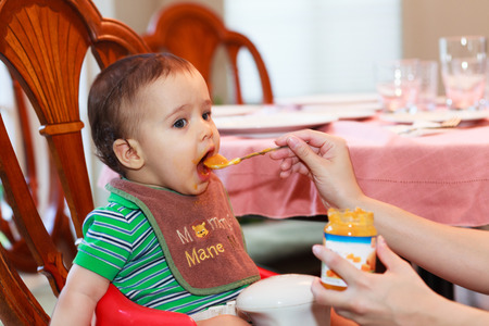 latin family: Hungry baby boy being fed a meal in a home setting. Stock Photo