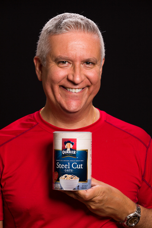 quaker: MIAMI, FLORIDA USA - FEBRUARY 4, 2014: Photo of a handsome middle age man holding a container of Quaker Steel Cut Oats used to promote lower cholesterol.