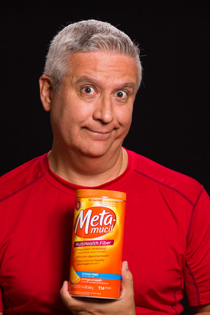 meta: MIAMI, FLORIDA USA - FEBRUARY 4, 2014: Photo of a handsome middle age man holding a Meta-mucil container used to treat constipation.