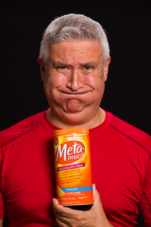 good cholesterol: MIAMI, FLORIDA USA - FEBRUARY 4, 2014: Photo of a handsome middle age man with a bloated expression holding a Meta-mucil container used to treat constipation.