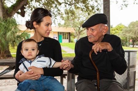 ni�os latinos: Hombre de ochenta a�os de edad avanzada, m�s viejo con la nieta en un escenario al aire libre.