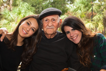 latino family: Elderly eighty plus year old man with granddaughters in a outdoor setting.