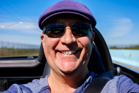 sex appeal: Handsome middle age man driving a convertible automobile on the highway. Stock Photo