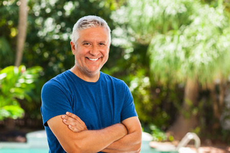 middle adult: Handsome unshaven middle age man outdoor portrait with a green background. Stock Photo