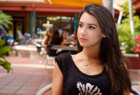 restaurant setting: Beautiful young woman outdoor in a restaurant setting.