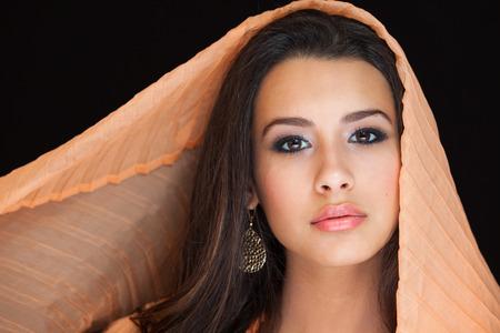 belle brunette: Belle jeune studio portrait de femme couverte d'un voile color� sur un fond noir. Banque d'images