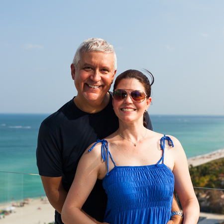 Happy middle age couple on a balcony overlooking Miami Beach.