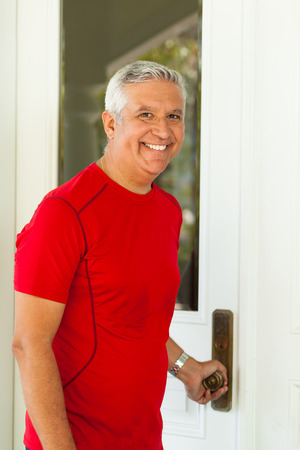 middle age man: Handsome middle age man opening the door to a residence.
