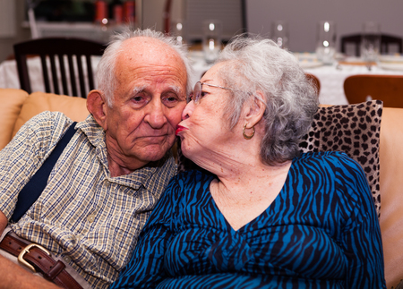 octogenarian: Elderly eighty plus year old couple in an affectionate pose in a home setting.