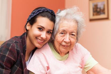 Ältere 80 Plus Jahre alte Großmutter mit Enkelin in einem Heim Einstellung.