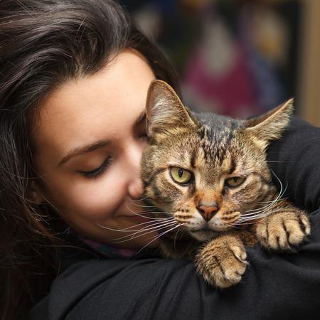 그녀의 애완 동물 tabby 고양이를 사랑하는 예쁜 여자. 스톡 콘텐츠 - 40569798