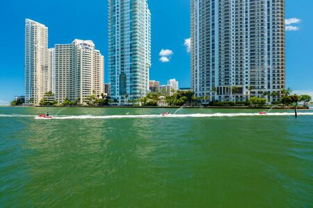 inlet: Miami, FL USA - June 19, 2015: Cityscape view of downtown Miami along the Miami River inlet with Brickell Key in the background and jet ski cruising by. Editorial