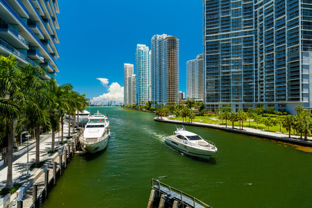 Downtown Miami along the Miami River inlet with Brickell Key in the background and yacht cruising by.