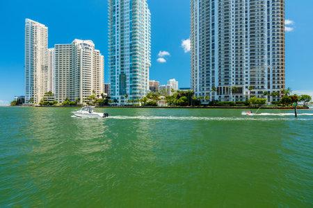 moto acuatica: Opinión del paisaje urbano de la ciudad de Miami, junto a la entrada del río de Miami con Brickell Key en el fondo y el barco y jet ski crucero por. Editorial