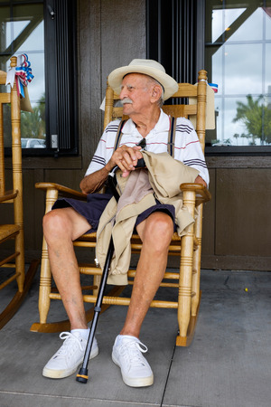 people sitting on chair: Elderly eighty plus year old man sitting on a rocking chair.