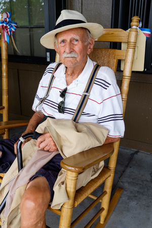 eighty: Elderly eighty plus year old man sitting on a rocking chair.