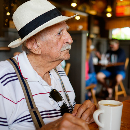 restaurant setting: Elderly eighty plus year old man wearing a hat in a restaurant setting.